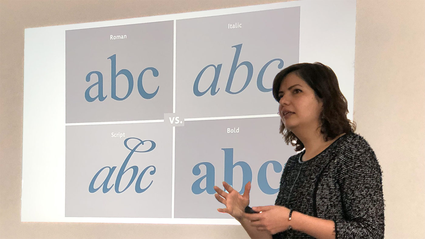 Nadine Chahine giving a presentation, in front of a slide showing the letters 'ABC' in different fonts.