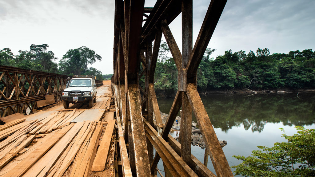A sightsavers 4x4 crosses a rickety bridge over a river in River Sess County, Liberia.