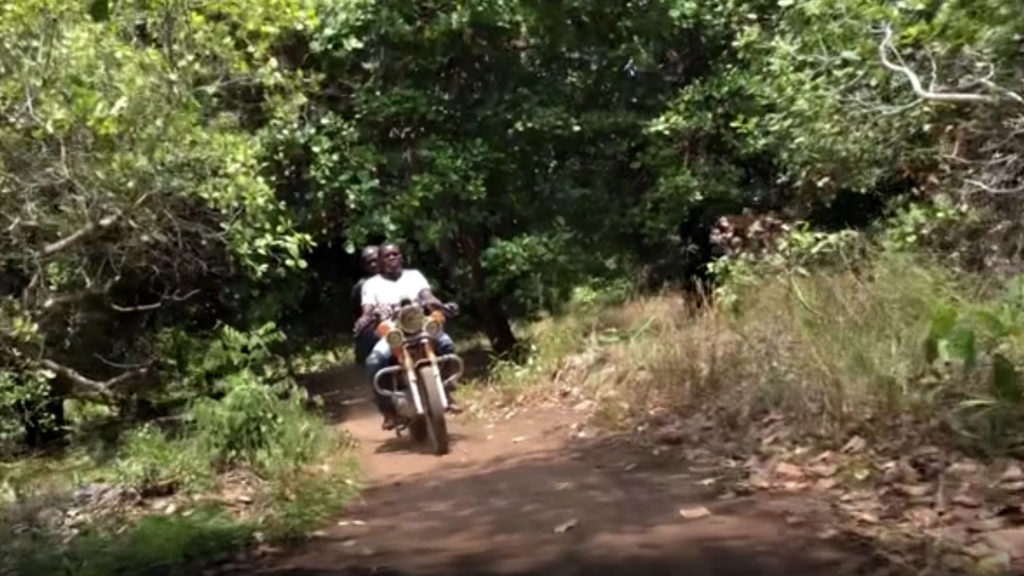 An eye health team on motorbikes ride through a wooded rural area in Tanzania.