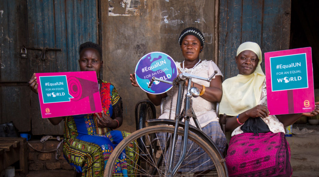 Three women, one of whom is using a wheelchair, holding up signs reading '#EqualUN for an equal world'.