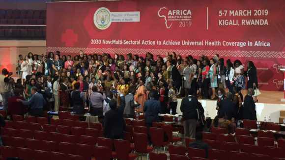A large crowd of people standing in a conference hall with a banner promoting the Africa Health Agenda International Conference.