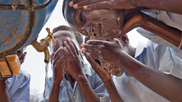 School children wash their faces.