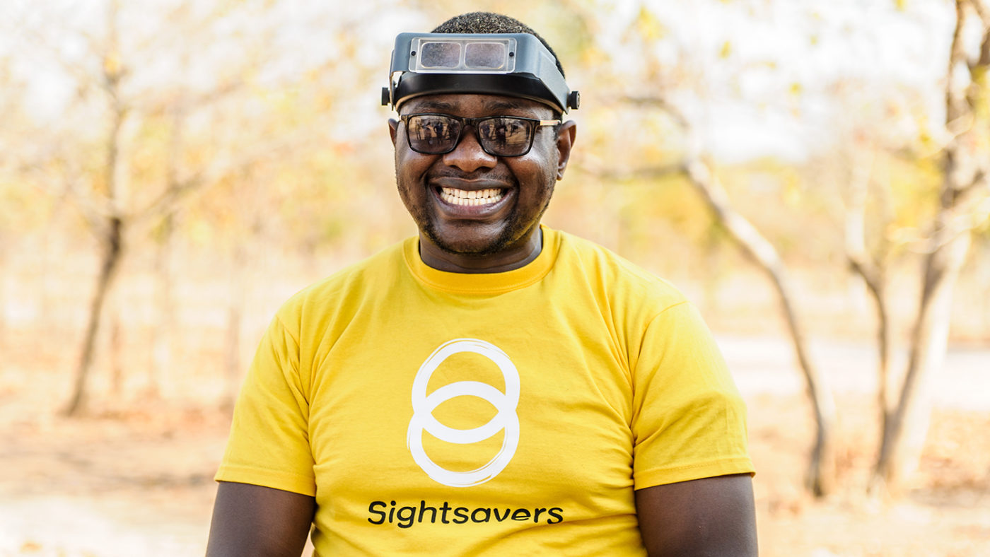 A man smiles, wearing a yellow Sightsavers tshirt.