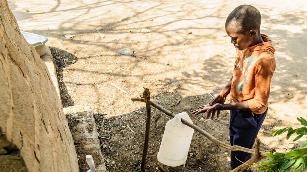 Kebby using the tippy tap outside his home in Zambia.