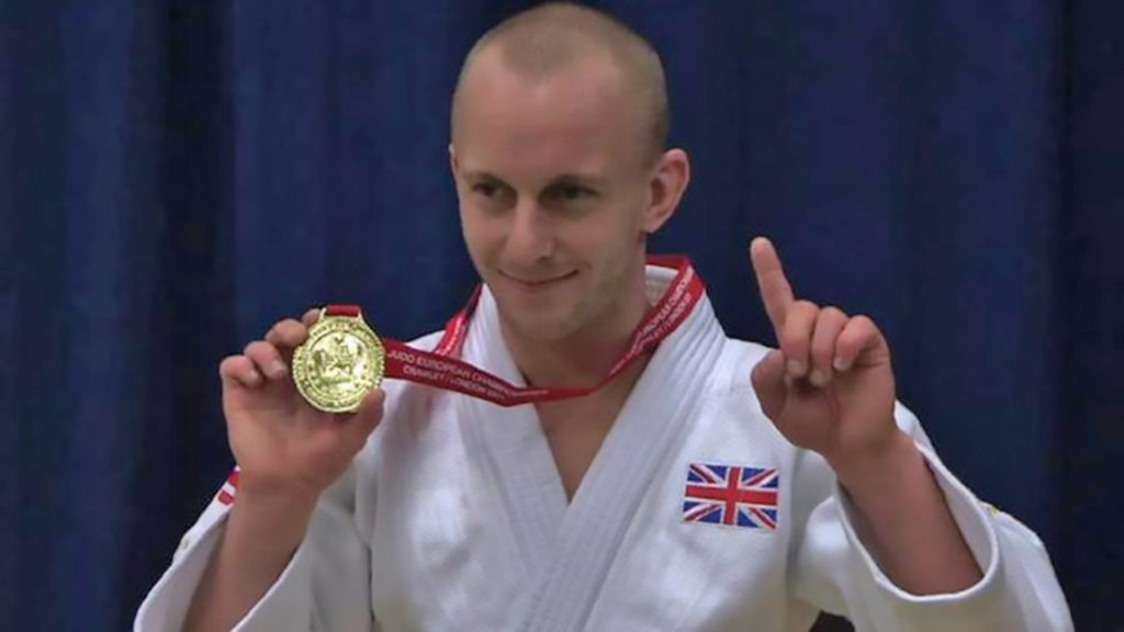 ben quilter holding a medal.