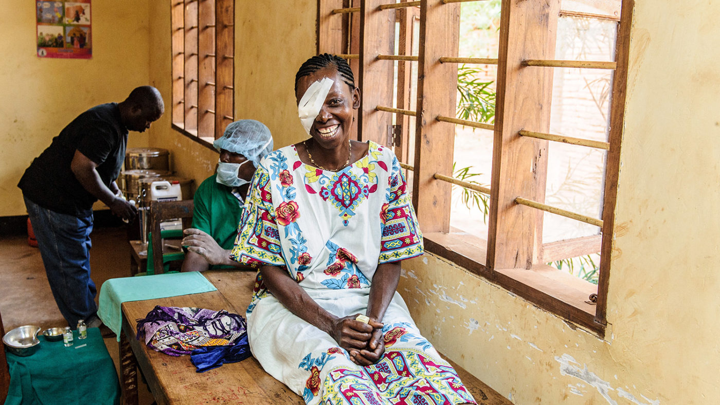 A woman has a big smile after receiving trachoma surgery