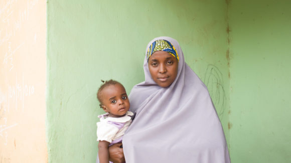 Aish Mukhtar, femal community designated distributor, poses with her daughter.