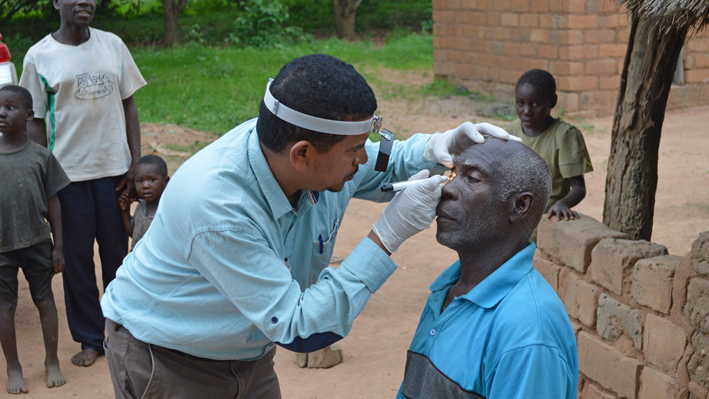 A doctor examine a man outside in rural Zambia.
