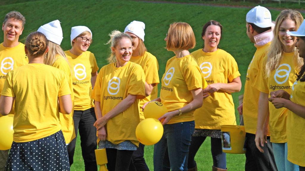 Group of people wearing Sightsavers yellow t-shirts.