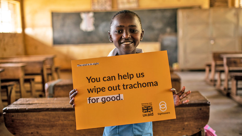Peace holds a sign saying 'You can help us wipe out trachoma for good.'