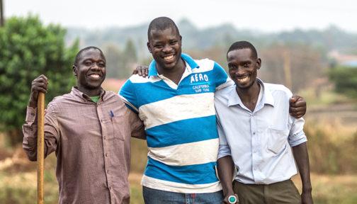 Three men holding walking sticks stand arm in arm.