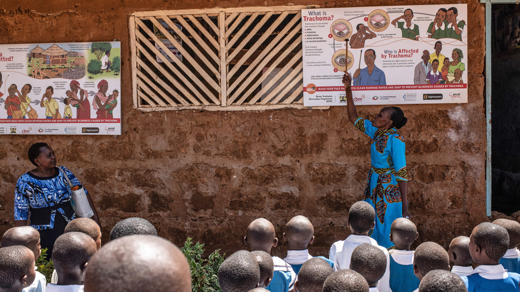 A teacher in Kenya points to a poster showing the word 'trachoma' as students watch.