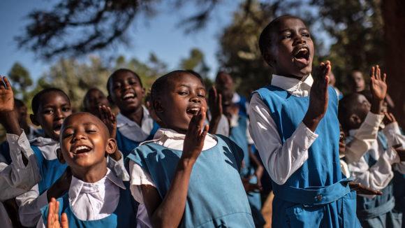 School children in Kenya sing songs outside in the sunshine.