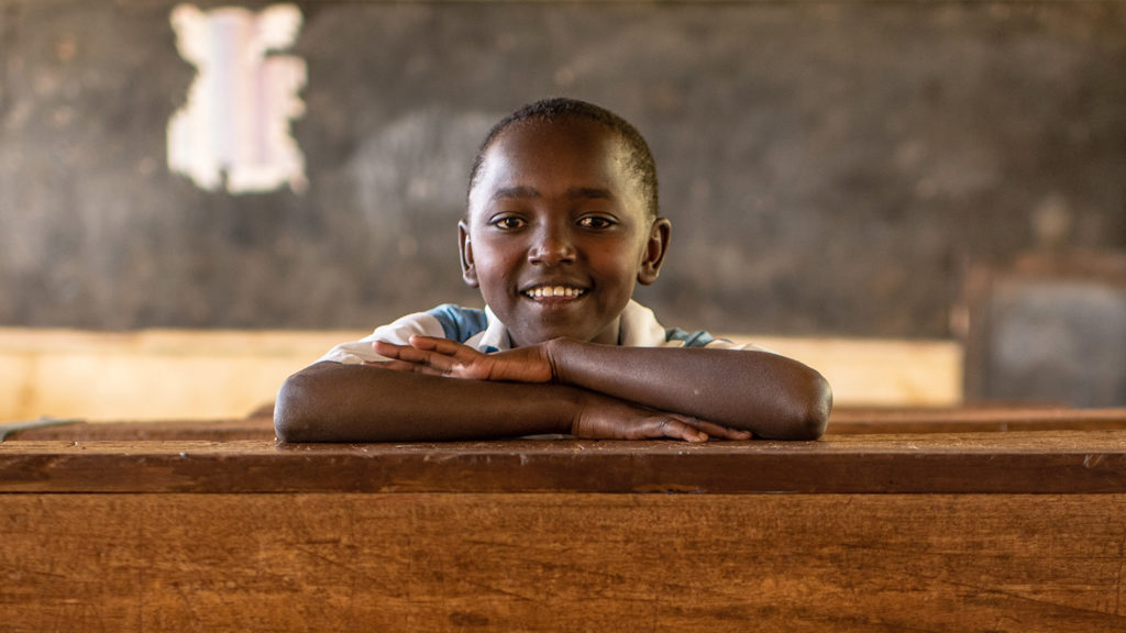 Peace sits at her desk in the classroom at school.