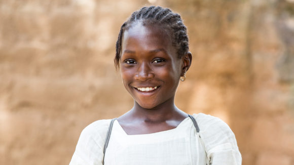 School student Promise smiles outside her school.