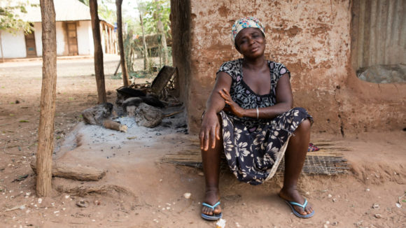 A woman affected by lymphatic filariasis (LF) sits outside her home.