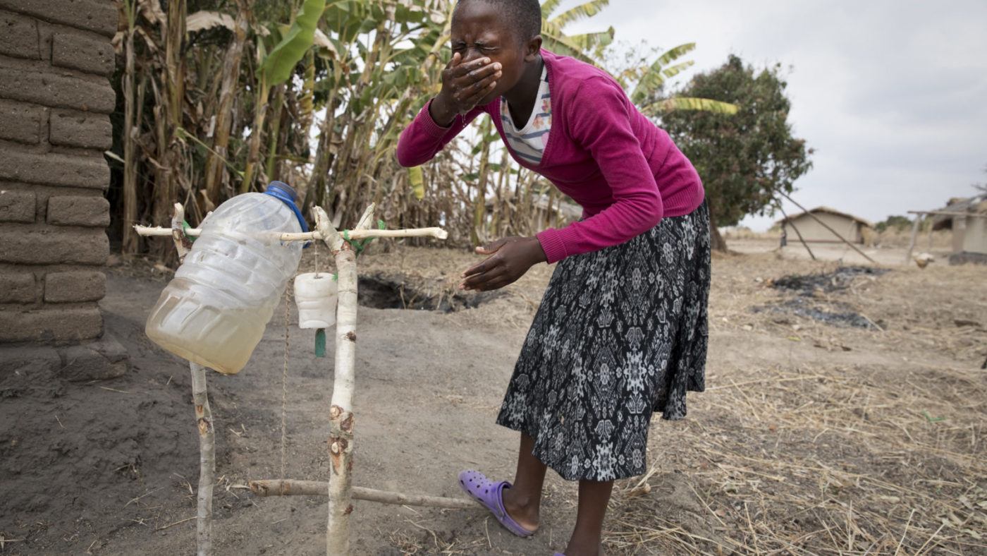 Schoolgirl and trachoma champion Safira Mwale shows how to wash her face with a tippy tap by her home near Kasungu in Malawi, August 29, 2018.