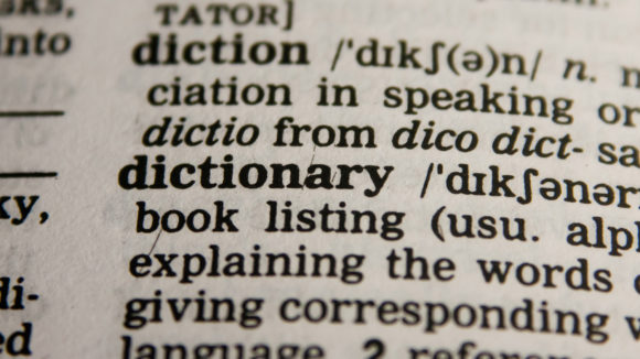 A close-up of a page from a dictionary, showing the definition of the word 'dictionary'.