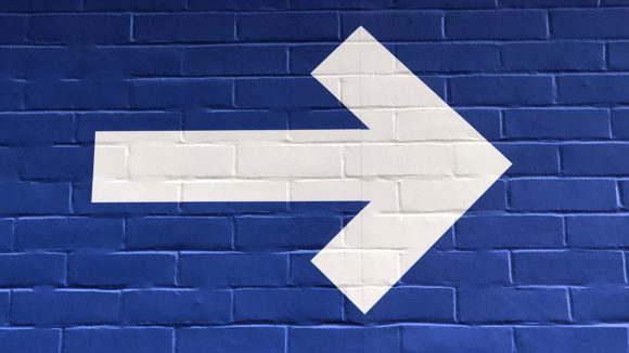 A white arrow symbol painted on a blue wall, pointing to the right.