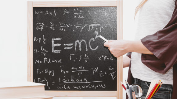 A man using a piece of chalk to point at a blackboard, which shows the text 'E=MC squared'.