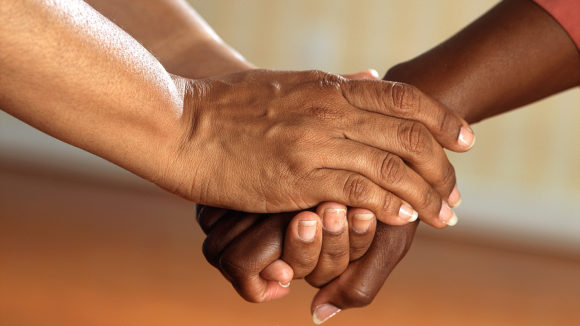 A close-up of two people's hands clasped together.