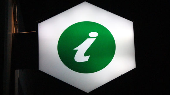 An illuminated sign showing a green 'i' symbol to denote information.