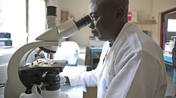 A man looks into a microscope in a lab.