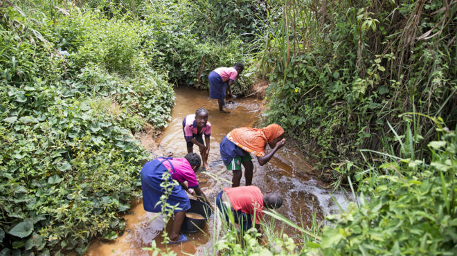 Children washing themselves in a stream.