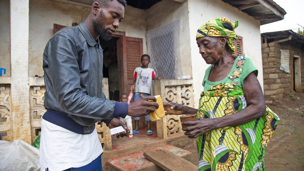 A lady receive medicine and food from a man.