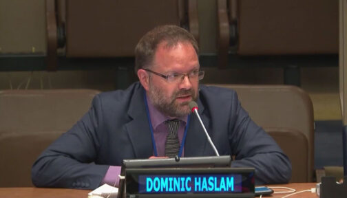 Dominic Haslam sat at a desk talking into a microphone