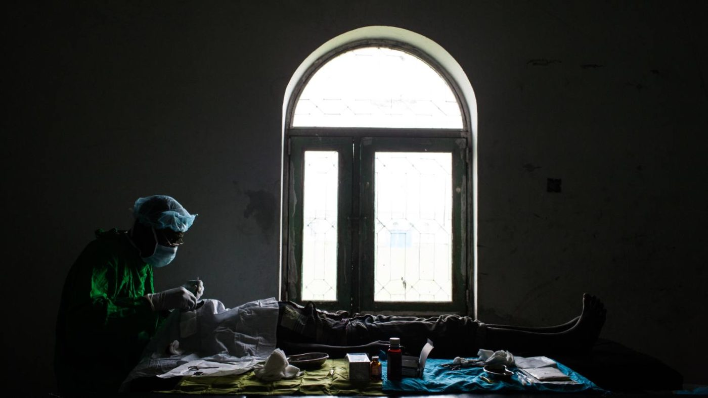 A surgeon operates, using only the light of a window, on a patient to save their sight from trachoma.