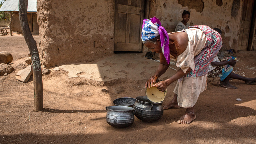 Abena washes a pot outside her home.