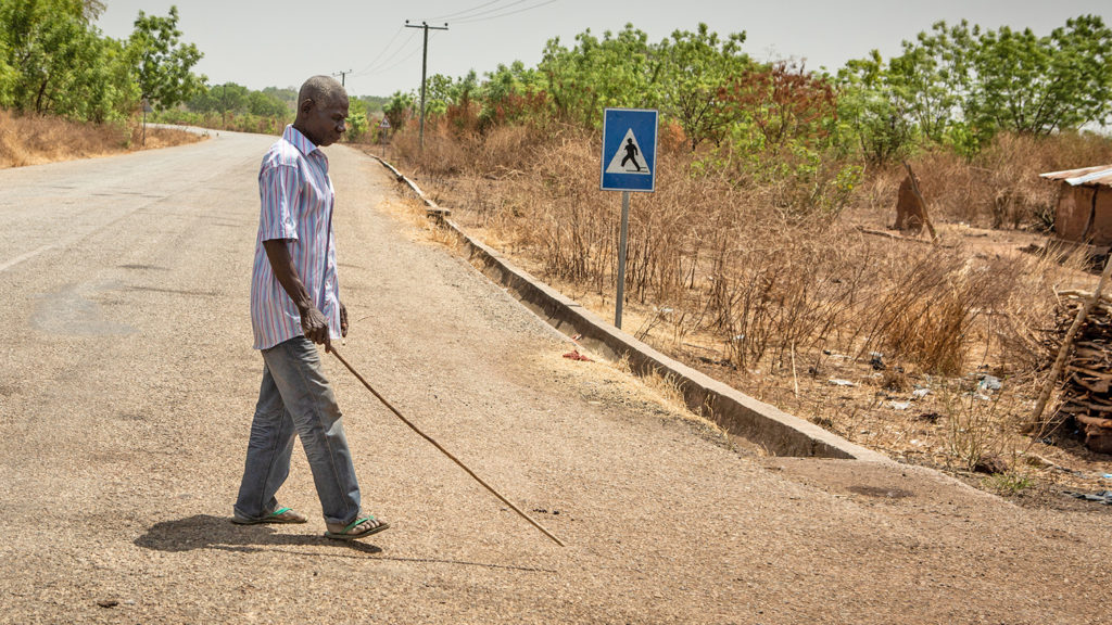 Akwasi walks with a stick near his home in Asubende.