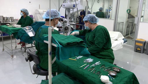 Two surgeons at work in the operating theatre at Mymensingh hospital. They're wearing green scrubs.