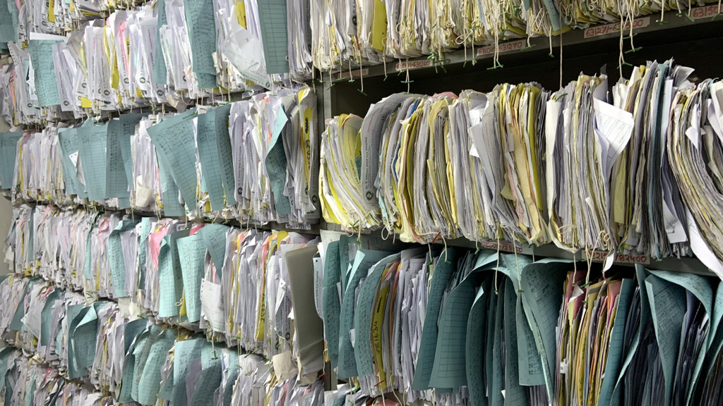 Thousands of paper files sit on shelves in the hospital.