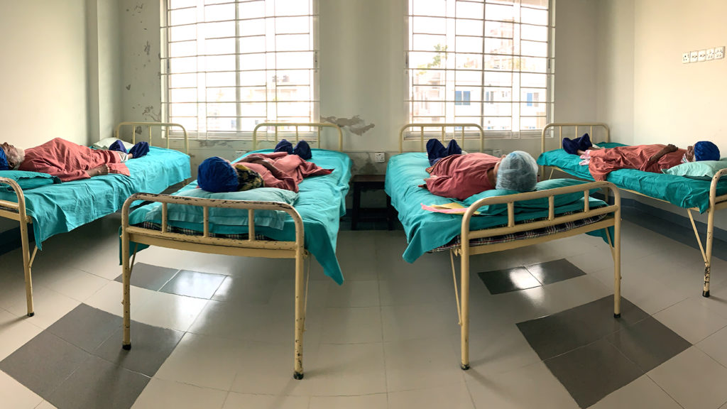 Four patients lie on beds in a hospital ward, with bright green sheets.