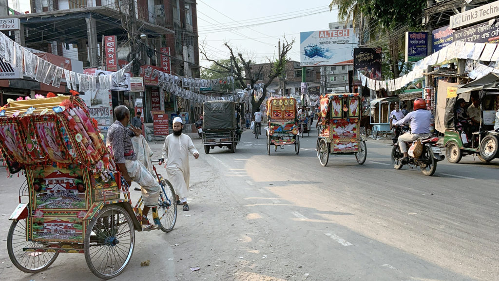A street scene from Bangladesh, showing rickshaws driving through a town area.