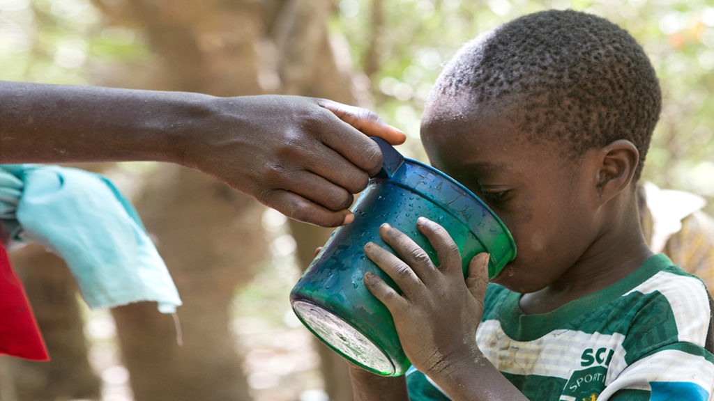 A child drinks water from a cup during a drug administration session in Nigeria.