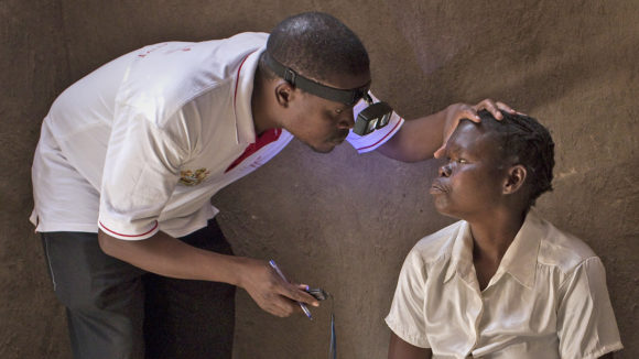 An eye health worker in Malawi checks a woman's eyes for signs of trachoma.