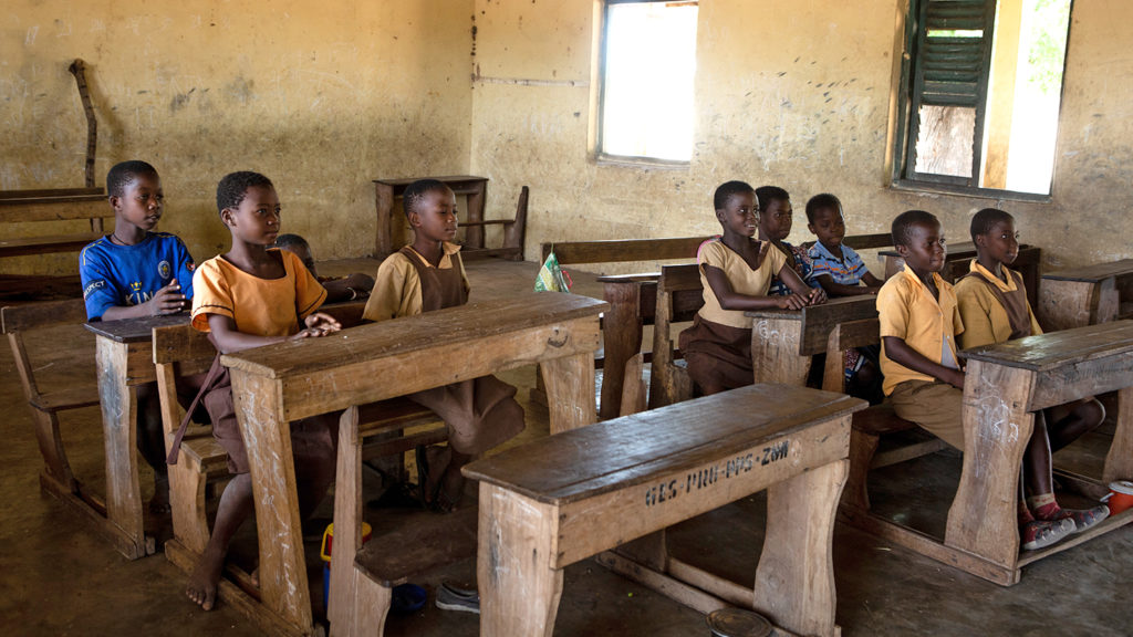 Students sit at wooden desks in their classroom in Asubende.