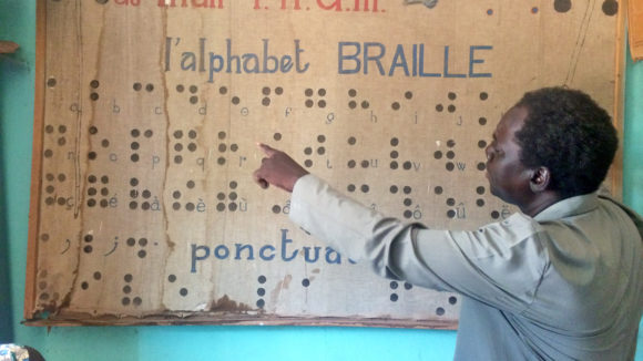 A teacher in Mali points to a sign showing the braille alphabet.