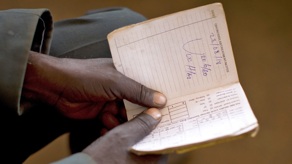 A close-up of a man holding some paperwork.