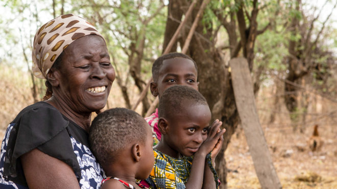 Mary, a volunteer in Ghana, sits with three smiling children.
