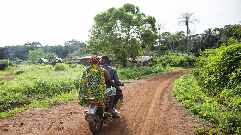 Two people riding a motorbike in rural Cameroon.