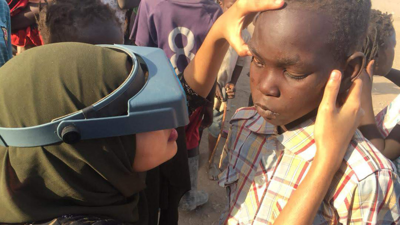 A trainee examines the eyes of child in Sudan as a part of a Tropical Data training workshop.