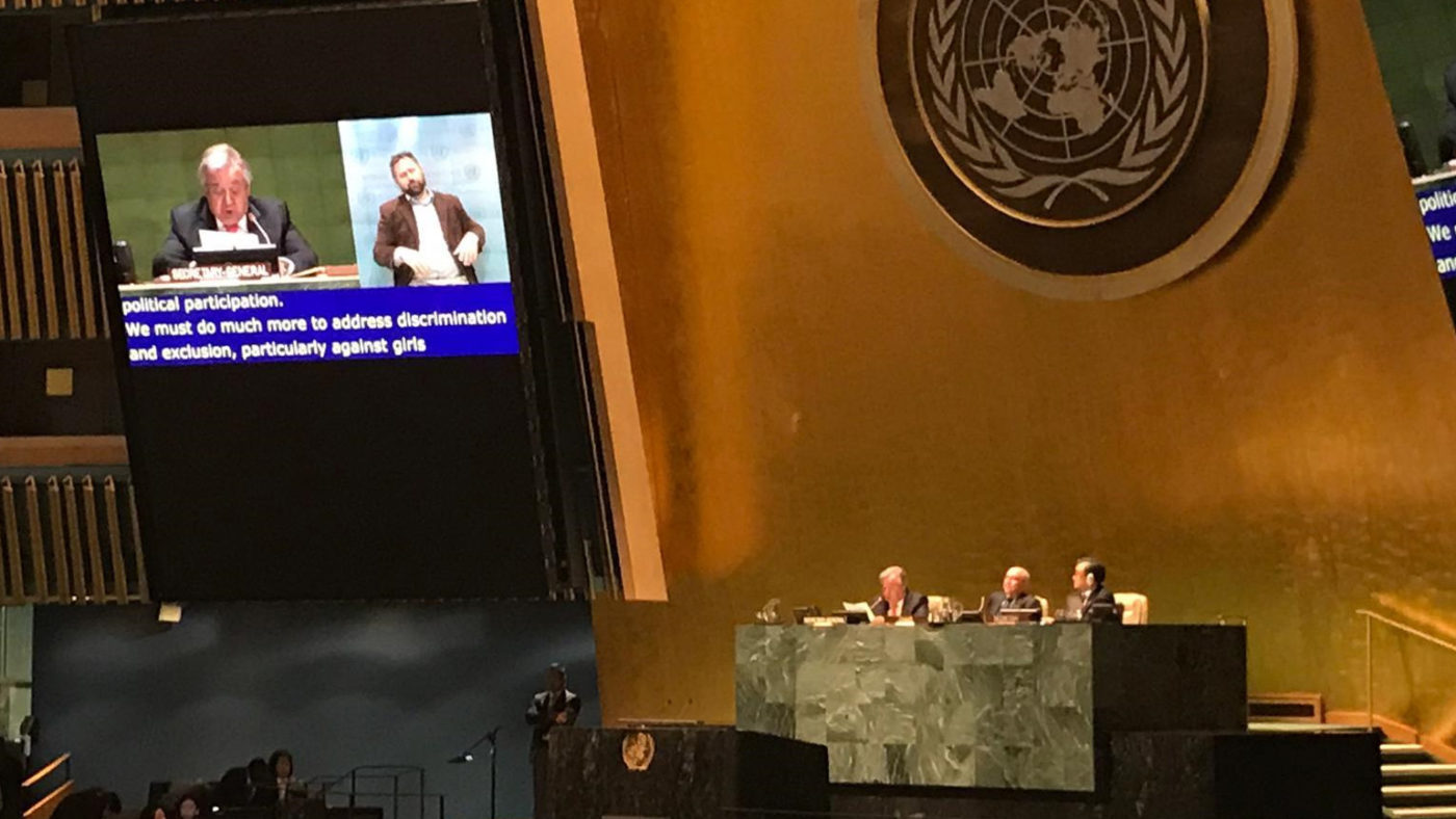 A wide view of a large debating chamber at the United Nations. The chamber is filled with people and a video screen shows captioned text.