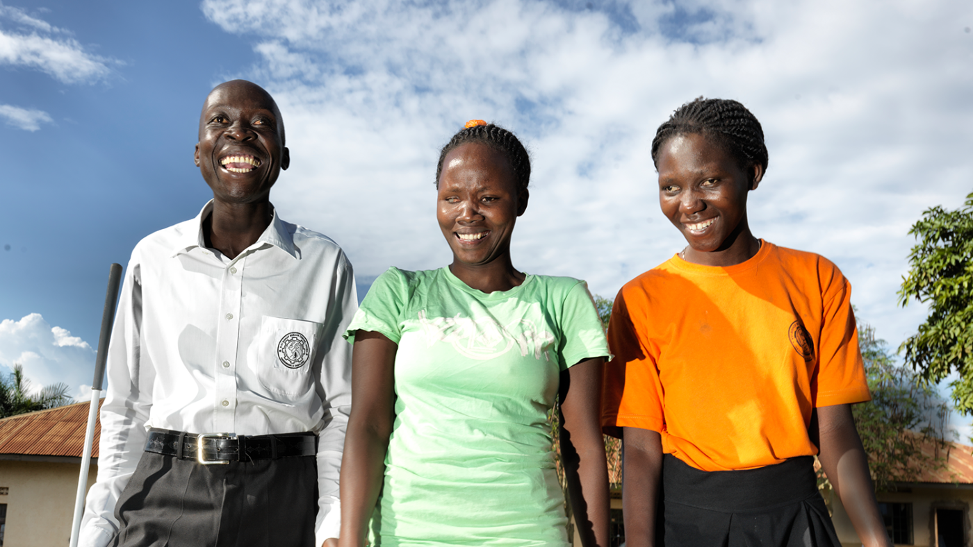 Three social inclusion participants are in a line smiling at the camera.