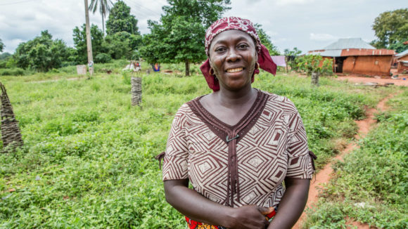 Julianah from Kogi, Nigeria stands outside a field near her home in Ajenejo, Kogi State Nigeria.