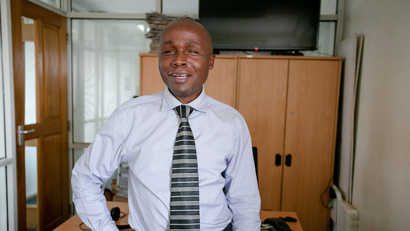 Deus Turyatemba stood in his office