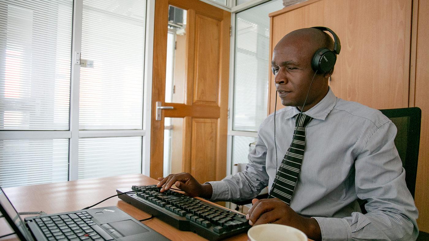Deus Turyatembaworking at his desk using assistive technology